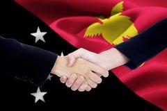 Poignée de main avec le drapeau de la Papouasie-Nouvelle-Guinée Images stock