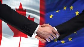 Poignée de main de Canada et d'Union européenne, amitié internationale, fond de drapeau clips vidéos
