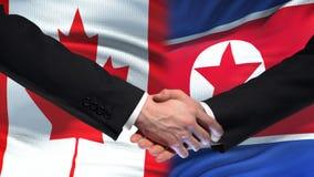 Poignée de main de Canada et de la Corée du Nord, amitié internationale, fond de drapeau banque de vidéos