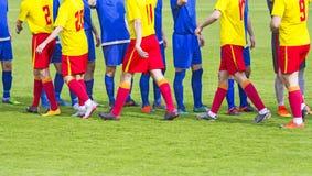 Poignée de main d'équipe de football deux sur le champ photo stock