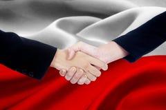 Poignée de main d'accord avec le drapeau de la Pologne Image stock
