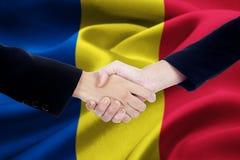 Poignée de main d'affaires avec le drapeau de la Roumanie Photographie stock libre de droits