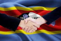 Poignée de main d'amitié avec le drapeau du Souaziland Photographie stock libre de droits