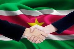Poignée de main d'amitié avec le drapeau du Surinam Image libre de droits