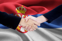 Poignée de main d'association avec le drapeau de la Serbie Photos stock