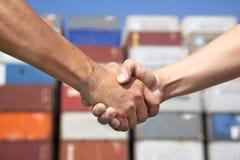 Poignée de main d'homme d'affaires avant la pile de conteneurs Images stock