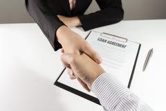 Poignée de main d'homme d'affaires et de femme d'affaires au-dessus de docu de convention de prêt Image stock