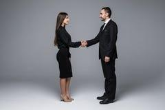 Poignée de main d'homme d'affaires et de femme d'affaires sur le fond gris photographie stock