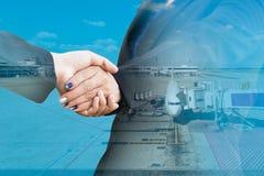 Poignée de main d'hommes d'affaires avec l'avion dans l'aéroport Photographie stock libre de droits