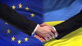Poignée de main d'Union européenne et de l'Ukraine, amitié internationale, fond de drapeau clips vidéos