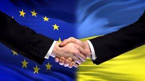 Poignée de main d'Union européenne et de l'Ukraine, amitié internationale, fond de drapeau image stock