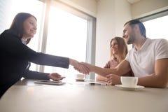 Poignée de main de couples et d'agent immobilier au-dessus de la table, affaire d'immobiliers photographie stock