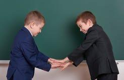 Poignée de main de deux amis, écolier élémentaire près du fond vide de tableau, habillé dans le costume noir classique, élève de  Photos libres de droits