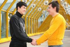 Poignée de main de deux amis sur la passerelle Photos libres de droits