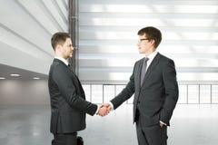Poignée de main de deux hommes d'affaires dans le lobby des affaires modernes Images libres de droits