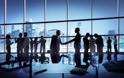 Poignée de main de deux hommes d'affaires ensemble au milieu Photographie stock
