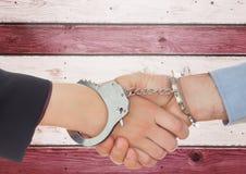 Poignée de main de deux personnes et attachement des menottes de Bu sur le fond en bois Photo libre de droits