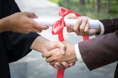 Poignée de main de félicitation reçue un diplôme image libre de droits