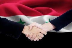 Poignée de main de négociation avec le drapeau de la Syrie Photographie stock