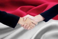 Poignée de main de négociation avec le drapeau du Monaco Photographie stock libre de droits