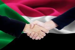 Poignée de main de négociation avec le drapeau du Soudan Photographie stock libre de droits