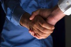 Poignée de main de poignée de main dans l'obscurité avec la faible luminosité photos libres de droits