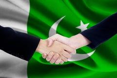 Poignée de main de réunion avec le drapeau du Pakistan Images stock