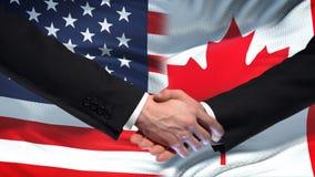 Poignée de main des Etats-Unis et du Canada, amitié internationale, fond de drapeau banque de vidéos