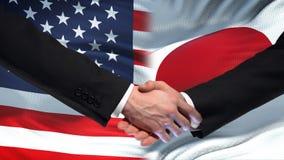 Poignée de main des Etats-Unis et du Japon, amitié internationale, fond de drapeau banque de vidéos