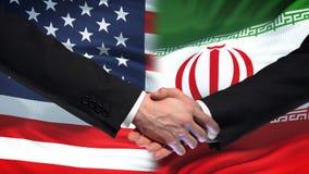 Poignée de main des Etats-Unis et de l'Iran, amitié internationale, fond de drapeau clips vidéos
