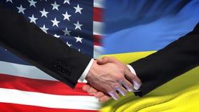 Poignée de main des Etats-Unis et de l'Ukraine, amitié internationale, fond de drapeau clips vidéos