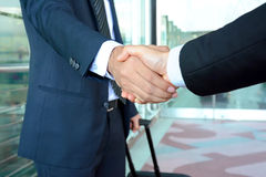 Poignée de main des hommes d'affaires à l'aéroport - concept de voyage d'affaires Images stock