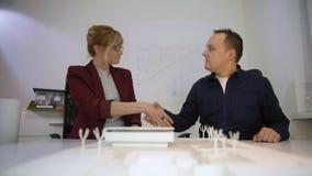 Poignée de main de deux architectes derrière un housemodèledans le bureau clips vidéos