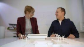 Poignée de main de deux architectes derrière un housemodèledans le bureau banque de vidéos