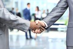 Poignée de main devant des gens d'affaires Image libre de droits