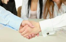 Poignée de main devant des gens d'affaires Photos stock