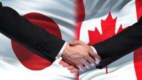 Poignée de main du Japon et de Canada, relations internationales d'amitié, fond de drapeau banque de vidéos