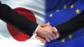 Poignée de main du Japon et d'Union européenne, amitié internationale, fond de drapeau banque de vidéos