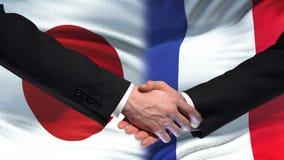 Poignée de main du Japon et de Frances, relations internationales d'amitié, fond de drapeau clips vidéos