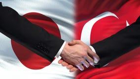 Poignée de main du Japon et de la Turquie, relations internationales d'amitié, fond de drapeau banque de vidéos