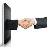 Poignée de main entre deux personnes par un périphérique mobile Image stock