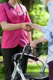 Poignée de main entre l'infirmière et handicapée Photographie stock libre de droits