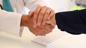 Poignée de main entre le docteur et le patient dans l'hôpital banque de vidéos