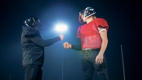 Poignée de main espiègle de deux sportifs sur un terrain de football clips vidéos
