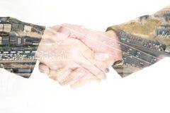Poignée de main et construction d'isolement d'affaires de double exposition Photo stock