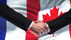 Poignée de main de Frances et de Canada, relations internationales d'amitié, fond de drapeau banque de vidéos