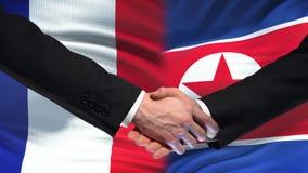 Poignée de main de Frances et de la Corée du Nord, amitié internationale, fond de drapeau banque de vidéos