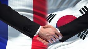 Poignée de main de Frances et de la Corée du Sud, amitié internationale, fond de drapeau clips vidéos