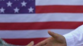 Poignée de main de gouvernement et de soldat des USA sur le fond de drapeau, respect pour le héros banque de vidéos