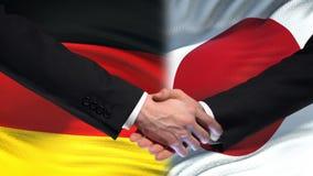 Poignée de main de l'Allemagne et du Japon, relations internationales d'amitié, fond de drapeau clips vidéos